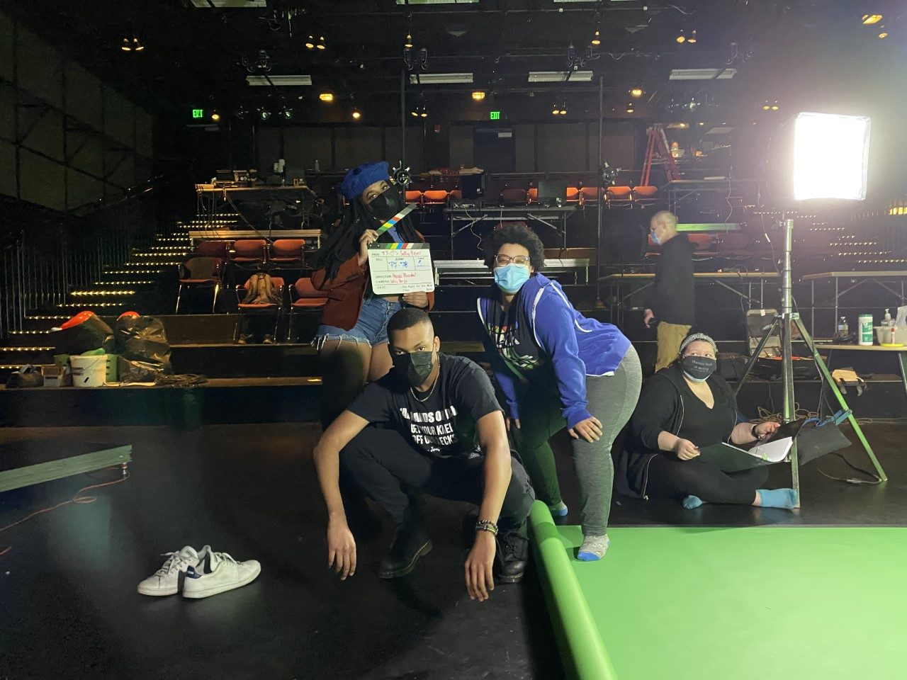A group of artists pose while filming on a set on stage